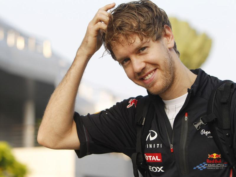 Red Bull Formula One driver Sebastian Vettel of Germany smiles as he arrives at the circuit for the first practice session for the Malaysian Formula One Grand Prix at Sepang, Malaysia. (AP Photo/Lai Seng Sin)