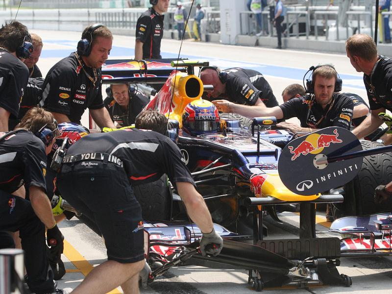 The pit crew for Red Bull Formula One driver Mark Webber of Australia work on his car during the first practice session at the Malaysian Formula One Grand Prix at Sepang, Malaysia. (AP Photo/Dita Alangkara)