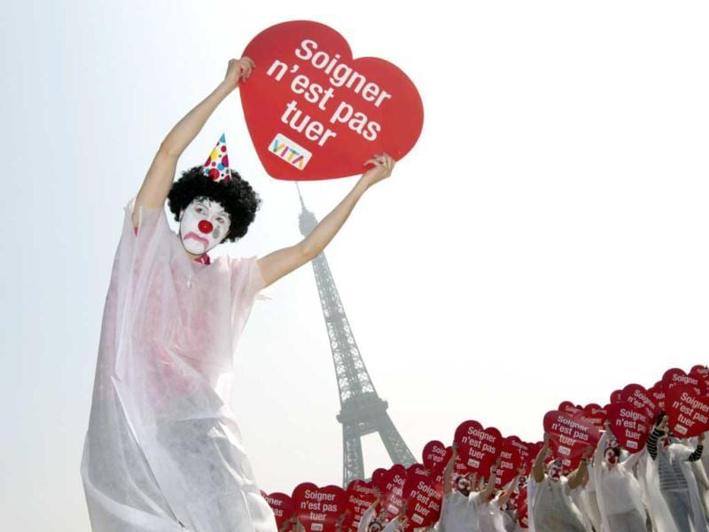 A protester, dressed up as a clown, holds a placard during a flash mob event organized by the 'Alliance VITA' association as part of their tour of France in solidarity with elderly people and against euthanasia in front of the Eiffel tower in Paris. Events take place in 50 French cities from March 5 to May 4, 2012. The placard reads 'To care is not to kill'. AFP Photo/Kenzo Tribouillard