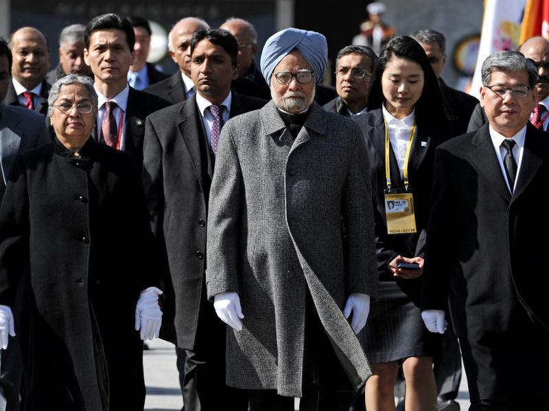 Prime Minister Manmohan Singh (C) and his wife Gursharan Kaur (L) visit the National Cemetery in Seoul ahead of the 2012 Seoul Nuclear Security Summit. The summit on atomic safety on March 26-27 will focus on the threat from nuclear-armed terrorists and follows one in Washington convened by US President Barack Obama in 2010 on the same subject. AFP Photo / Nicolas Asfouri