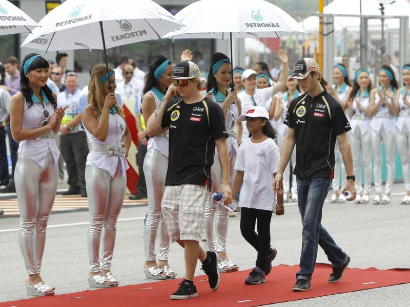 Lotus Formula One teammates Kimi Raikkonen (L) of Finland and Romain Grosjean of France walk out for the drivers parade prior to the start of the Malaysian Formula One Grand Prix at Sepang. AP Photo/Lai Seng Sin