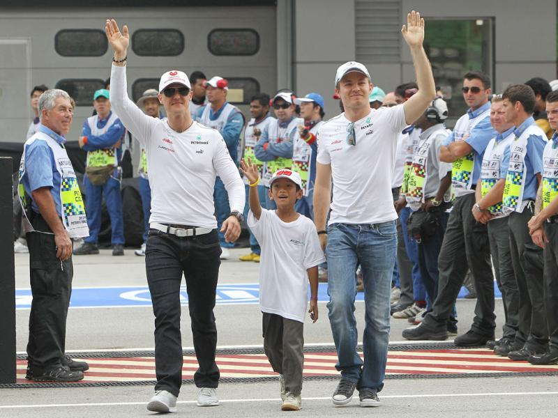 Mercedes teammates and compatriots Michael Schumacher (L) and Nico Rosberg (R) walk out for the drivers parade prior to the start of the Malaysian Formula One Grand Prix at Sepang. AP Photo/Achmad Ibrahim