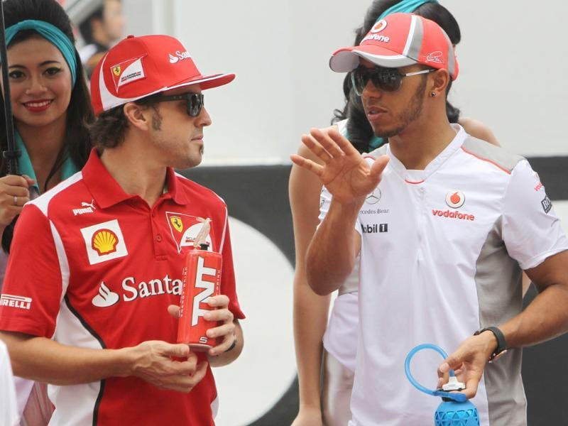 Ferrari Formula One driver Fernando Alonso (L) of Spain talks with McLaren Formula One driver Lewis Hamilton of Britain during the drivers parade prior to the start of the Malaysian Formula One Grand Prix at Sepang. AP Photo/Achmad Ibrahim