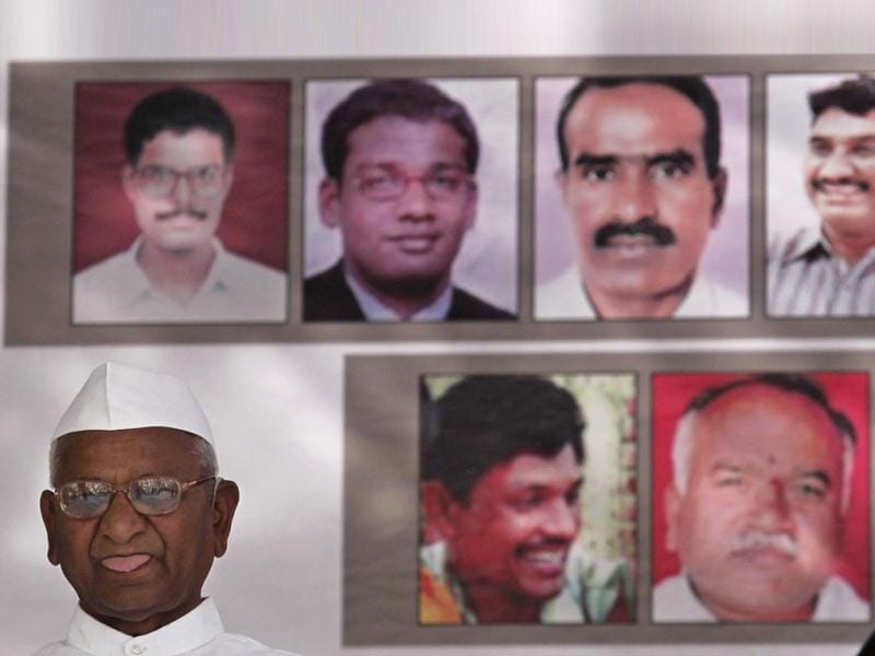 Veteran social activist Anna Hazare sits under the portraits on display of men who according to anti-corruption activists died while fighting corruption over the years, during his day-long hunger strike against corruption in New Delhi. REUTERS/Adnan Abidi