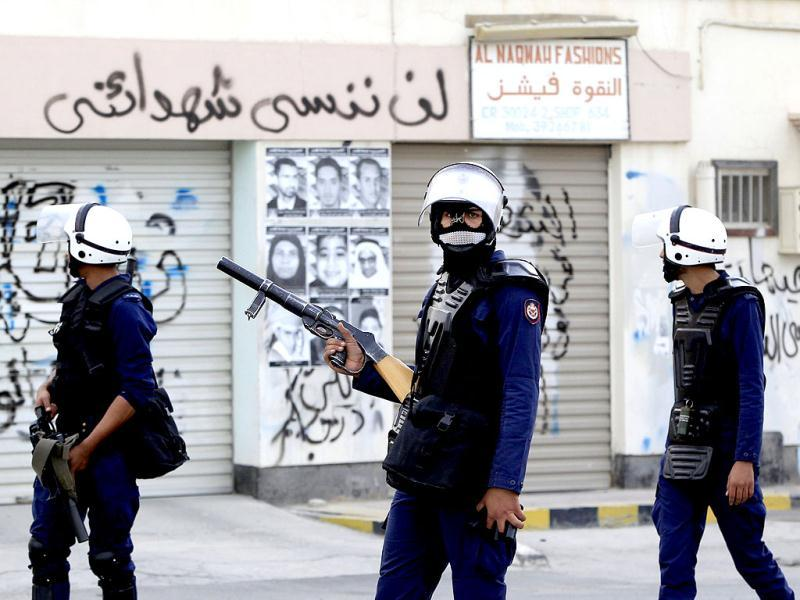 Riot police walk past anti-government and anti-F1 graffiti during clashes in the district of Sitra in Bahrain. Reuters/Ahmed Jadallah