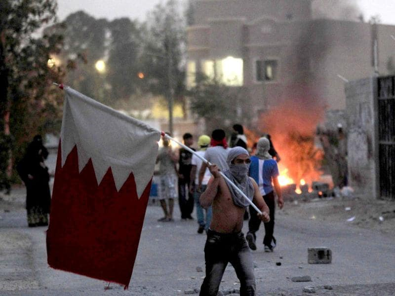 An anti-government protester waves the Bahraini flag during clashes with riot police in the district of Sitra. Reuters/Ahmed Jadallah