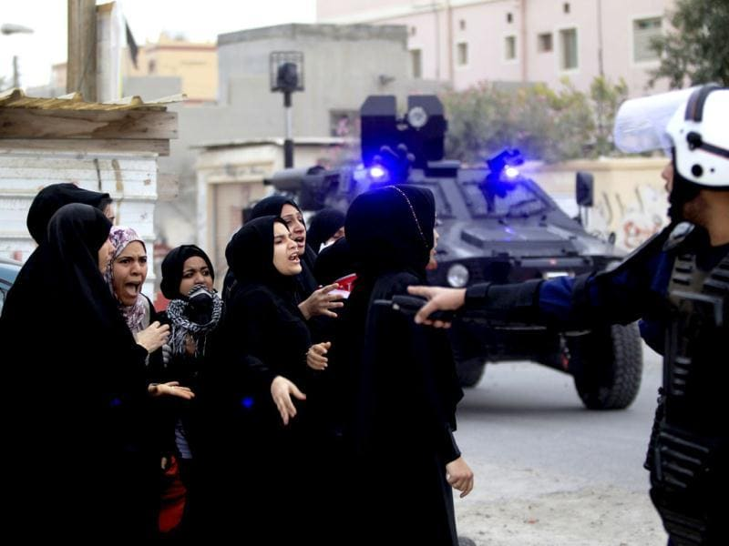 Female anti-government protesters argue with a riot policeman during clashes in the district of Sitra. Reuters/Ahmed Jadallah