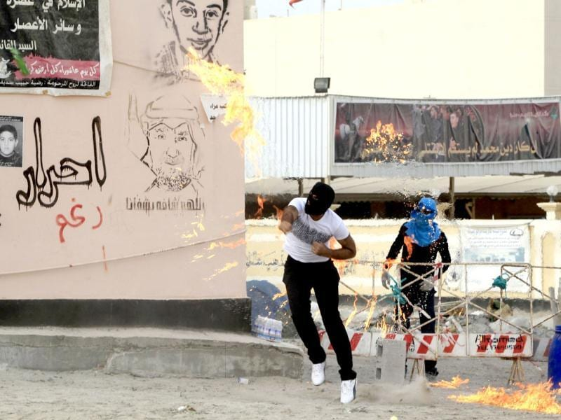 An anti-government protester throws a Molotov cocktail at riot policemen and their armoured personnel carrier during clashes in the district of Sitra in Bahrain. Reuters/Ahmed Jadallah