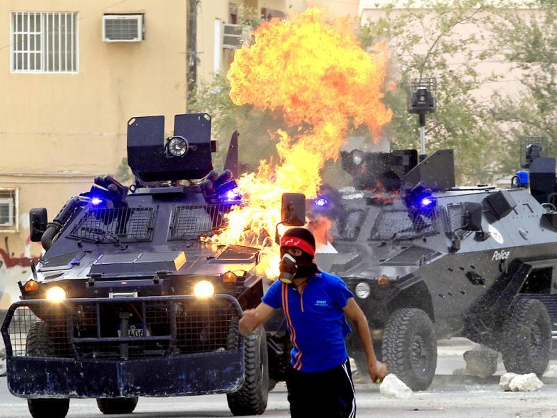 An anti-government protester runs a way after he threw a Molotov cocktail at riot policemen and their armoured personnel carriers during clashes in the district of Sitra in Bahrain. Reuters/Ahmed Jadallah