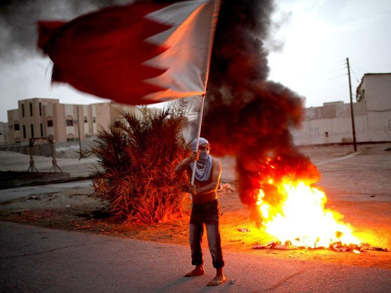 An anti-government protester waves Bahrain's national flag during clashes with riot police in the district of Sitra in Bahrain. Demonstrators were protesting in Sitra against the government holding the F1 Grand Prix in April. Reuters/Ahmed Jadallah