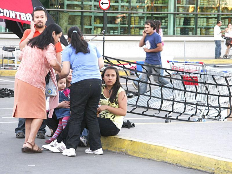 People gather outside a shopping mall after an earthquake was felt in Talca, Chile. A magnitude-7.2 earthquake has struck just off the coast of central Chile, prompting an emergency evacuation order for people living near the ocean in case it spawns a tsunami. (AP Photo/Fabian Suazo)