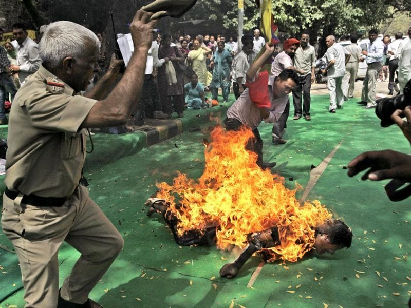 A police officer and a protester try to extinguish the fire as a Tibetan man is engulfed in flames after self-immolating at a protest in New Delhi. AP Photo/Manish Swarup