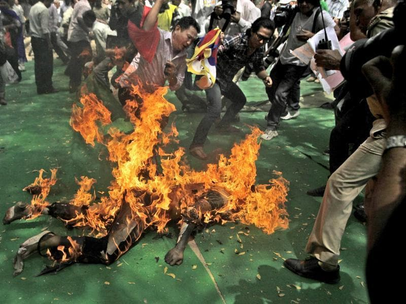Fellow protesters try to extinguish the fire as a Tibetan man, identified as Jampa Yeshi, is engulfed in flames after self-immolating at a protest in New Delhi. AP Photo/Manish Swarup