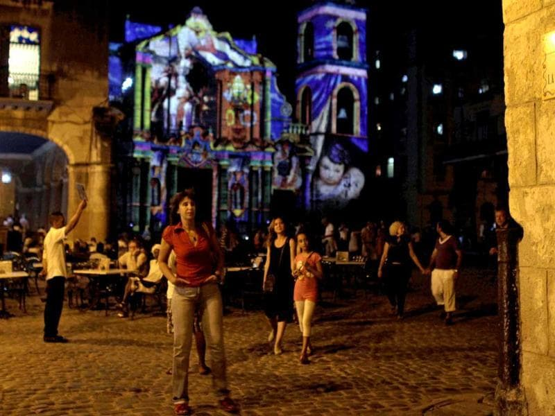 People walk past Havana's cathedral as images of Pope Benedict XVI by the French-Italian artist Gaspare Di Caro are projected on its facade in Havana, Cuba. AP Photo/Franklin Reyes