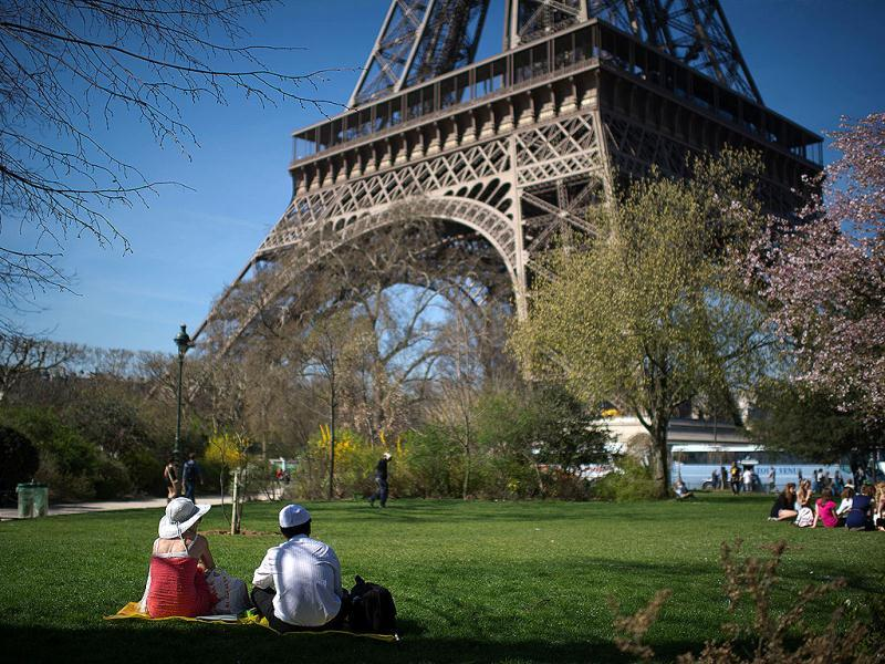 A couple is having a lunch on the grass of the Champs de Mars under a great sun in Paris. AFP Photo/Martin Bureau