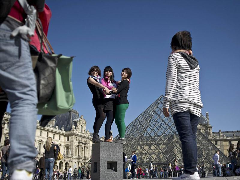 Tourists pose for a picture under a great sun in the Carrousel du Louvre in Paris. AFP Photo/Fred Dufour