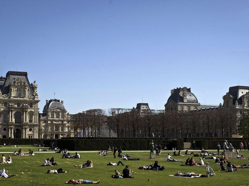 People enjoy the sun on the grass of the Carrousel du Louvre in Paris. AFP Photo/Fred Dufour
