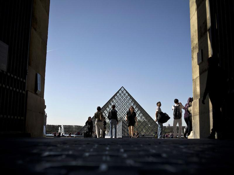 People walk under a great sun in the Carrousel du Louvre in Paris. AFP Photo/Fred Dufour