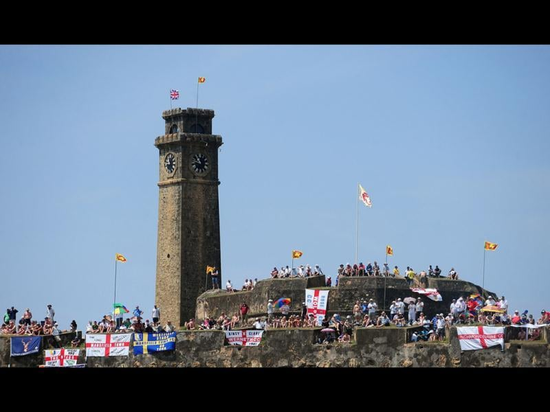 England cricket team fans watch the second day of the opening Test Match between Sri Lanka and England from the top of the 14th century Dutch fort near the Galle International Stadium in Galle. AFP PHOTO/ LAKRUWAN WANNIARACHCHI