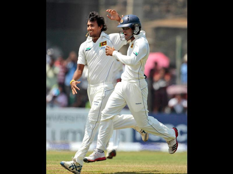 Sri Lanka's bowler Suranga Lakmal, left, celebrates the dismissal of England's batsman Alistair Cook, unseen, with teammate Dinesh Chandimal, right, during the second day's play of their first test cricket match in Galle, Sri Lanka, . (AP Photo/ Eranga Jayawardena