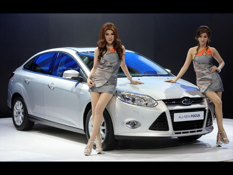 Thai models pose next to a Ford All-New Focus on display at the 33rd Bangkok International Motorshow. AFP Photo/Pornchai Kittiwongsakul