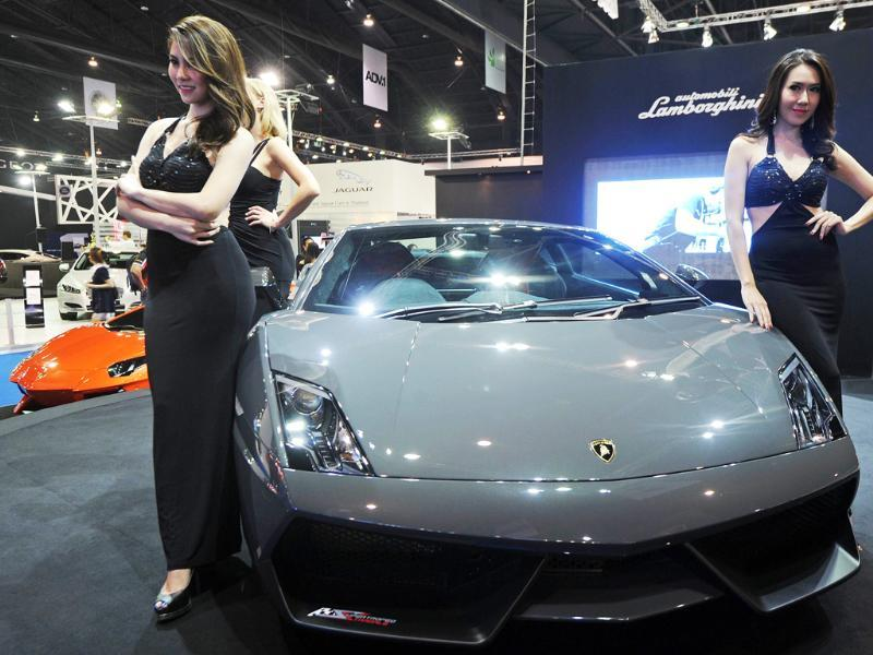 Models pose next to a Lamborghini Gallardo LP 570-4 Super Trofeo Stradale on display at the 33rd Bangkok International Motorshow. AFP Photo/Pornchai Kittiwongsakul
