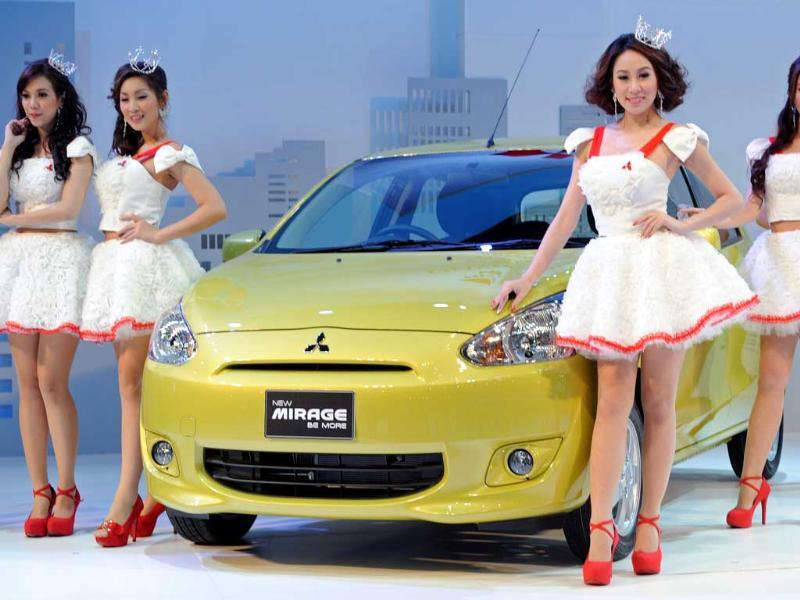 Thai models pose next to the new Mitsubishi Mirage on display at the 33rd Bangkok International Motorshow in Bangkok. AFP Photo/Pornchai Kittiwongsakul