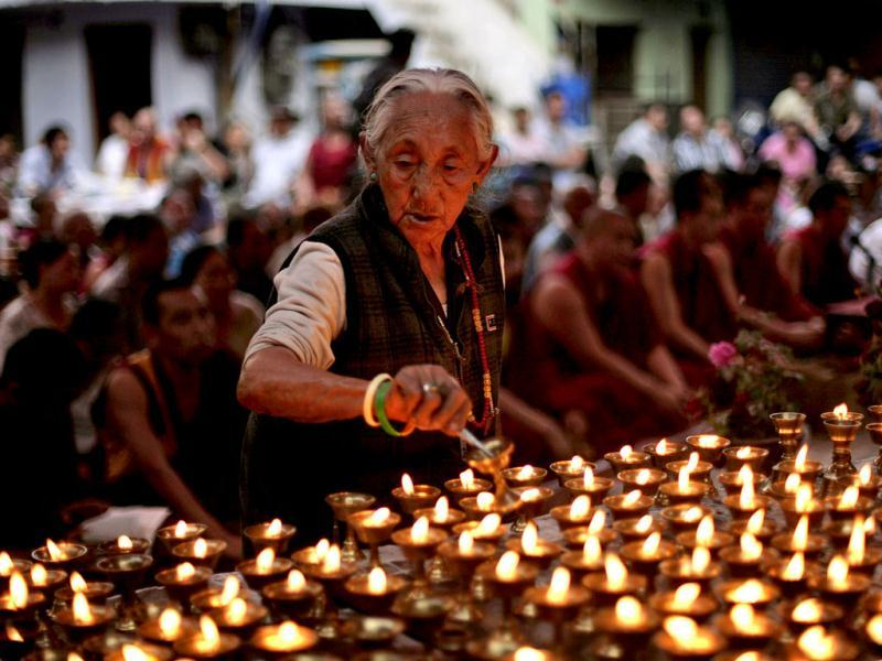 An elderly exiled Tibetan lights lamps during a special prayer session for Tibetan Jampa Yeshi who immolated himself on Monday during a protest, at a Tibetan Refugee settlement in New Delhi. (AP Photo/Altaf Qadri)