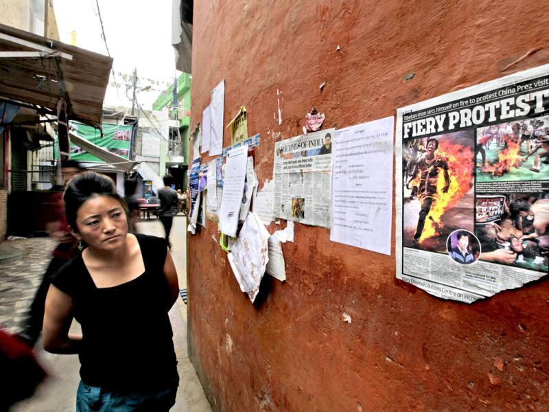 An exile Tibetan woman looks at a newspaper page with photos of Tibetan Jampa Yeshi who immolated himself on Monday during a protest, at a Tibetan Refugee settlement in New Delhi. (AP Photo/Altaf Qadri)