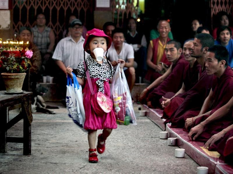 A young Tibetan exile girl, biting a disposable cup, walks past Tibetan Buddhist monks during a special prayer session for Tibetan Jampa Yeshi who immolated himself on March 26 during a protest, at a Tibetan Refugee settlement in New Delhi. (AP Photo/Altaf Qadri)