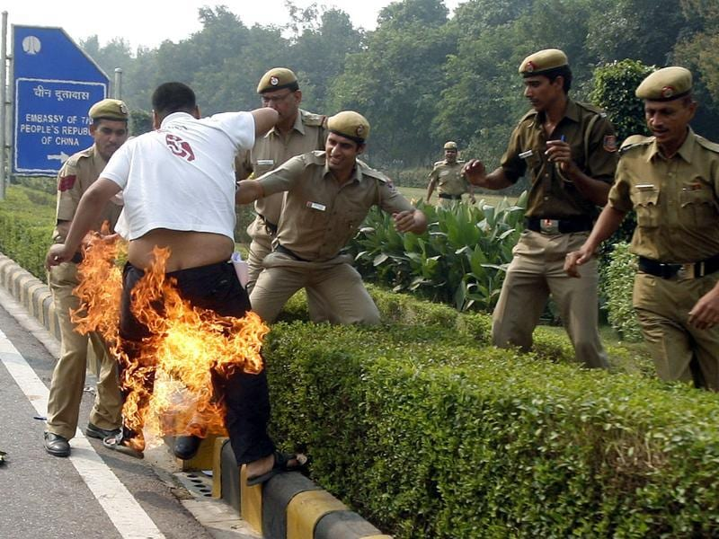 Police try to douse flames on a Tibetan demonstrator after he tried to self immolate himself during a protest in front of the Chinese embassy in New Delhi on November 4, 2011. Reuters/Parivartan Sharma