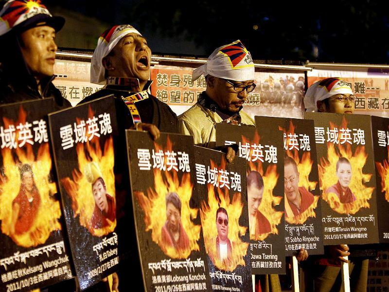 Tibetans display portraits of people who killed themselves in self-immolation take part in a candlelight vigil in Taipei on February 8, 2012. Reuters/Pichi Chuang