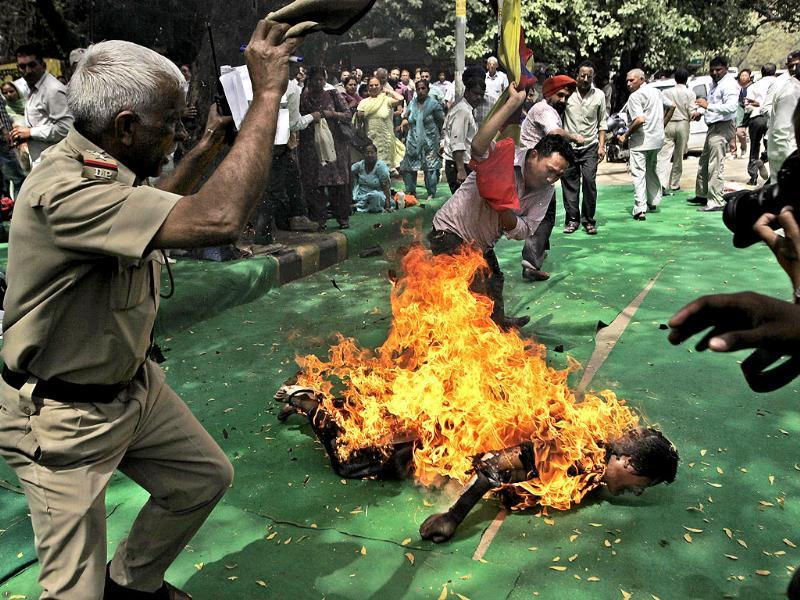 A police officer and a protester try to extinguish the fire as a Tibetan man is engulfed in flames after self-immolating at a protest in New Delhi ahead of Chinese President Hu Jintao's visit to the country on March 26, 2012. AP Photo/Manish Swarup