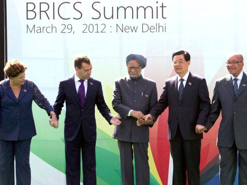 Prime Minister Manmohan Singh (C) joins hands with Brazilian President Dilma Rousseff, Russian President Dmitry Medvedev, Chinese President Hu Jintao and South African President Jacob Zuma at the 4th BRICS Summit in New Delhi. PTI/Kamal Singh