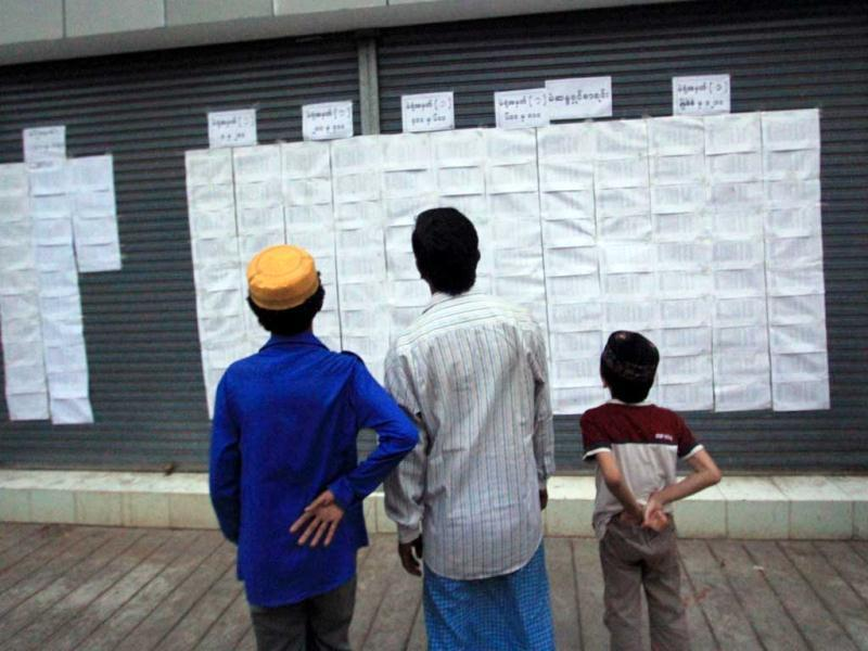 People look at a list with candidates' names, at a polling station in Yangon. AFP/Ye Aung Thu