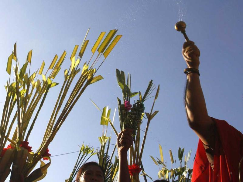 A priest sprinkles holy water as a faithful wave their palm branches while participating in a Palm Sunday procession in Manila. Reuters Photo/Romeo Ranoco