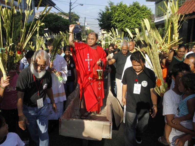 A priest, wheeled on a makeshift cart, sprinkles holy water as devotees wave their palm branches while participating in a Palm Sunday procession in Manila. Reuters Photo/Romeo Ranoco