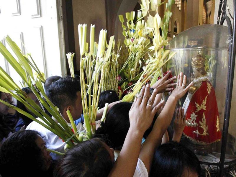 Churchgoers, with their woven palms, touch the glass where a baby Jesus doll, called Sto. Nino, is encased during Palm Sunday mass in Manila. Reuters Photo/Romeo Ranoco