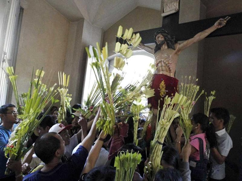 Churchgoers wave their woven palms in front of a crucifix during Palm Sunday mass in Manila. Reuters Photo/Romeo Ranoco