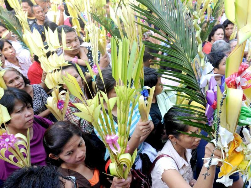 Dovetees wave their palm fronds as a priest blesses them during Palm Sunday mass in Manila. AFP photo/Jay Directo