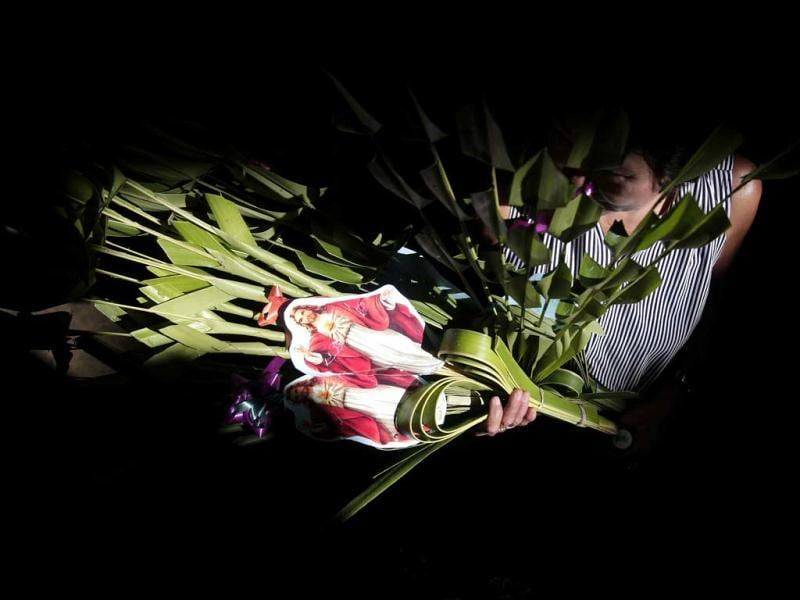 A devotee carries palm fronds with an image of Jesus Christ during Palm Sunday rites outside Santo Nino Parish Church in Manila. AP Photo/Aaron Favila