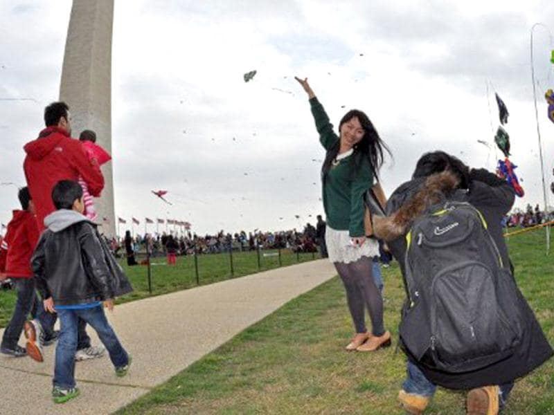 A Japanese tourist poses in front of the Washington Monument during the annual Blossom Kite Festival in Wasington, DC. The event is part of the National Cherry Blossom Festival which this year celebrates 100 years of friendship between Japan and the United States. AFP PHOTO/Eva Hambach