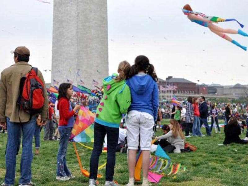 Girls watch a scuba diver kite float past the Washington Monument during the annual Blossom Kite Festival in Wasington, DC. The event is part of the National Cherry Blossom Festival which this year celebrates 100 years of friendship between Japan and the United States. AFP PHOTO/Eva Hambach