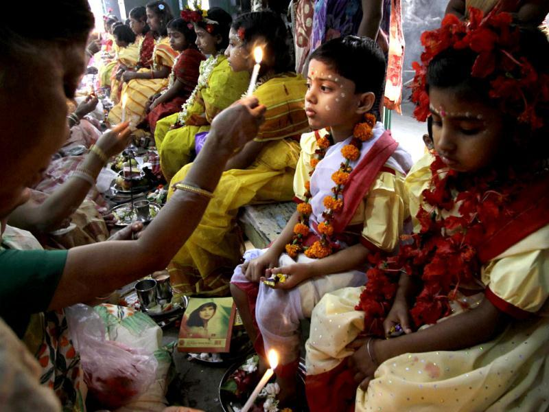 A Hindu devotee worships young girls as they sit together dressed as
