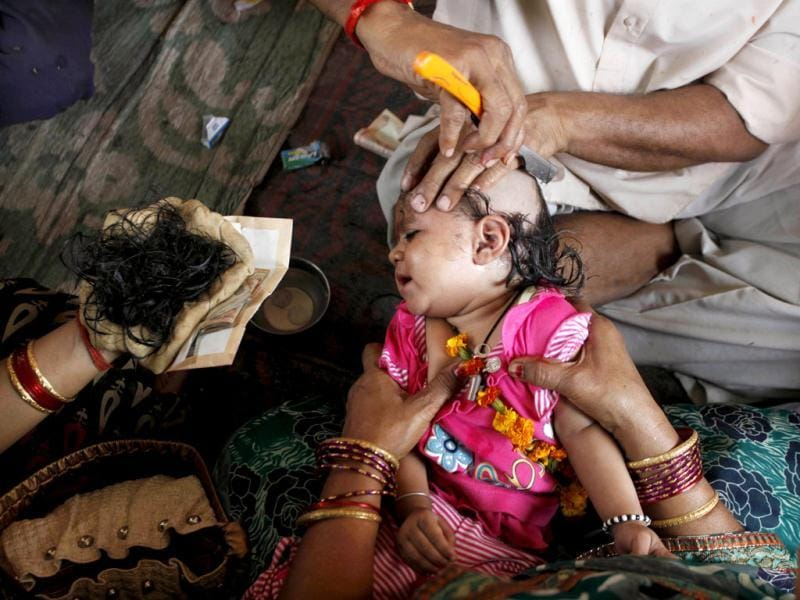 A barber cuts the hair of a young girl as part of a ritual during the Hindu festival of Ram Navami, at a temple in Allahabad. (AP Photo/Rajesh Kumar Singh)