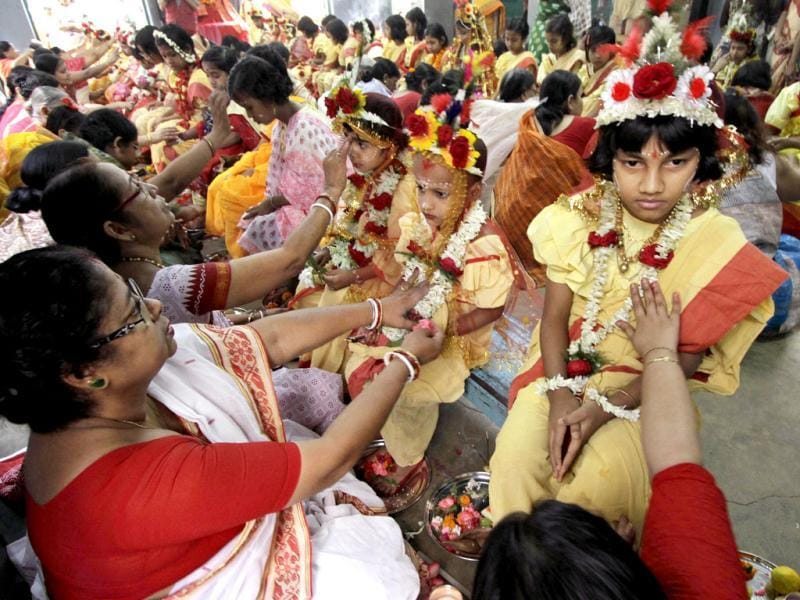 Hindu devotees worship young girls as they sit together dressed as