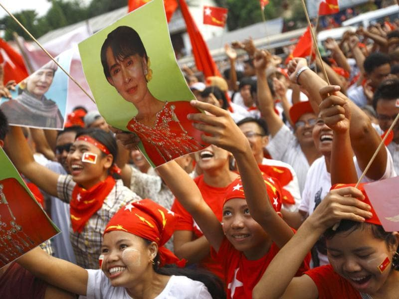 Supporters of the National League for Democracy (NLD) party cheer holding a portrait of Myanmar pro-democracy leader Aung San Suu Kyi as they watch increasing votes on a screen at the roof of the NLD office in Yangon. Myanmar voted on Sunday in its third election in half a century. REUTERS/Staff