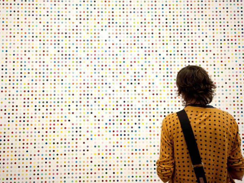 A woman looks at a spot painting by British artist Damien Hirst during the opening of his solo exhibition showcasing work spanning over two decades at the Tate Modern in central London. AFP Photo/Ben Stansall