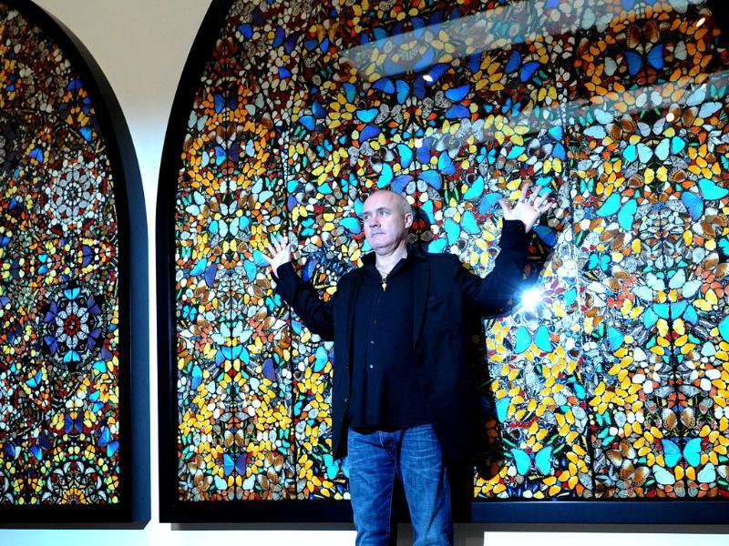 British artist Damien Hirst poses for photographers with a creation entitled Doorways to the Kingdom of Heaven 2007 during the opening of his solo exhibition showcasing work spanning over two decades at the Tate Modern in central London. AFP Photo/Carl Court