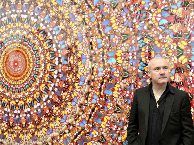 British artist Damien Hirst poses next to his painting I Am Become Death, Shatterer of Worlds (2006), at the Tate Modern gallery in London. Hirst's retrospective show runs from April 4 to September 9. Reuters/Toby Melville